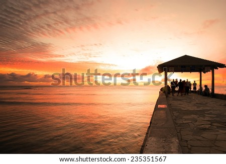 Sunset watchers gather at end of Waikiki beach cement pier to enjoy tropical sunset - stock photo