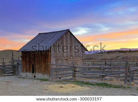 Sunset with a rustic old barn and corral, Utah, USA. - stock photo