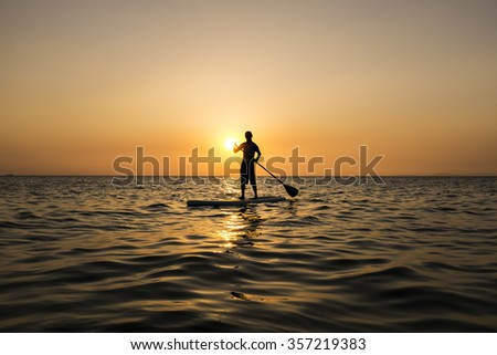 sunset with a surfer - stock photo