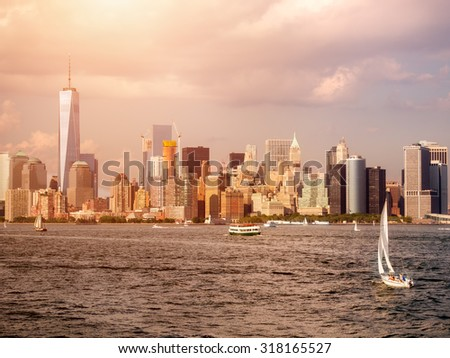 Sunset with a view of the New York Harbor and the Manhattan skyline - stock photo