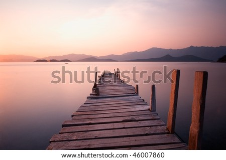 Sunset with a wooden bridge with long exposure - stock photo