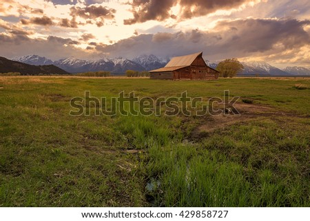 Sunset with an old barn in a field, Wyoming, USA. - stock photo