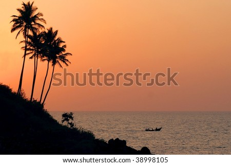 Sunset with boat in goa India - stock photo