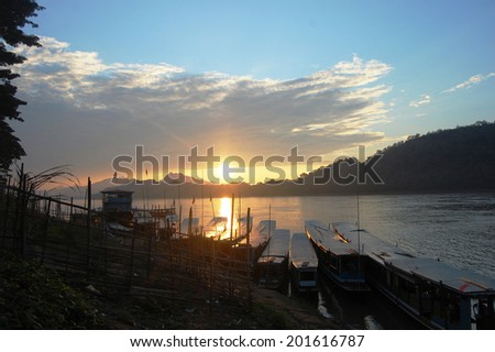 Sunset with Fishing boat on Mekong river in Luang Prabang City at Loas Lao People s Democratic Republic  - stock photo