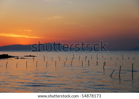 Sunset with fishing poles in the foreground, Rabbit Island, Cambodia - stock photo