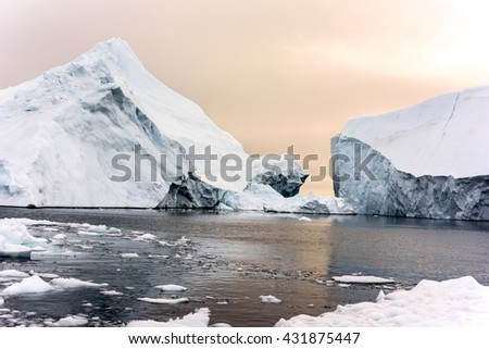 sunset with iceberg at arctic ocean in greenland - stock photo