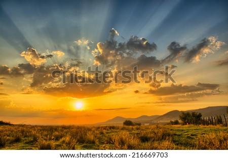 Sunset with intense light rays. - stock photo
