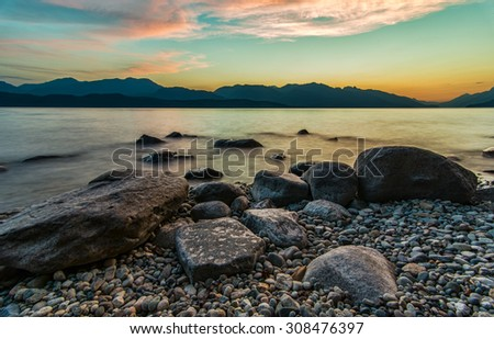 Sunset with lakeside rocks and distant mountains. - stock photo