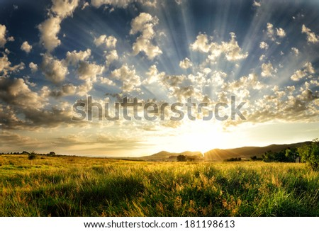 Sunset with light rays filling up the sky - enhanced rays. - stock photo