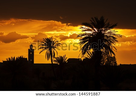 Sunset with mosque and date palm silhouettes, with dark clouds. - stock photo