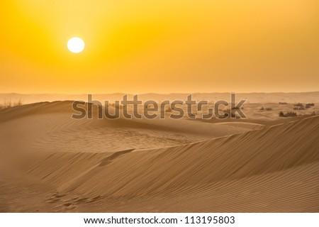 Sunset with sand dunes in desert - stock photo