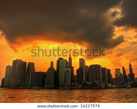 sunset with sky like fire over lower manhattan - stock photo