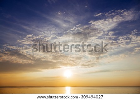 Sunset with sun rays and clouds in the sea