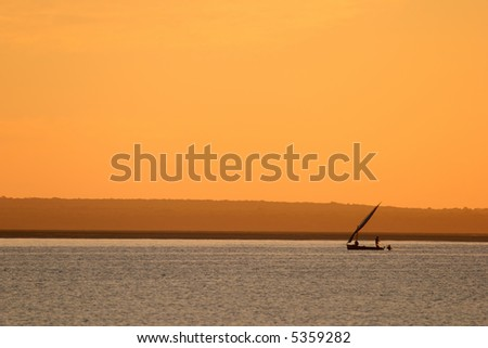 Sunset with traditional sail boat called a dhow, Vilanculos coastal sanctuary, Mozambique - stock photo