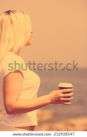 Sunset with young woman with fresh cup of tea or coffee on the beach - stock photo