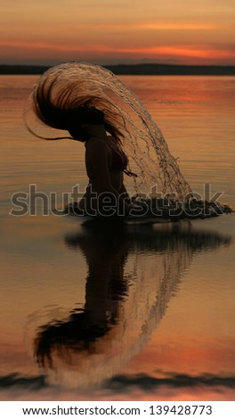 sunset yoga woman on sea coast with reflection  Silhouettes of young girl jumping in ocean at sunset - stock photo