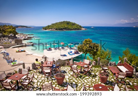 Sunshade umbrellas and deckchairs on the beautiful Ksamil beach, Albania. - stock photo