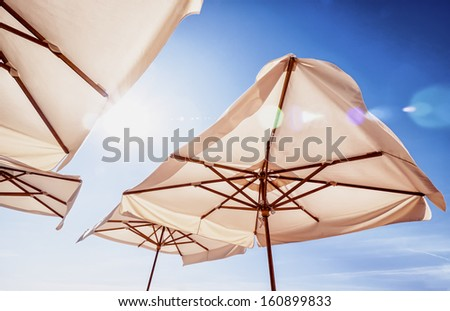 sunshades in front of blue sky - stock photo