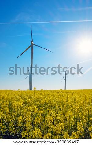 Sunshine, rapeseed and windwheels seen in rural Germany - stock photo