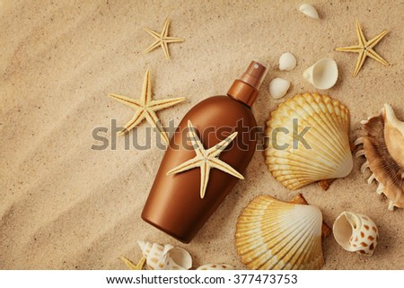suntan cream bottle on sand beach - stock photo