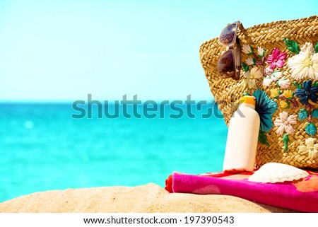 Suntan cream,hat,bag and sunglasses by the sea.  - stock photo