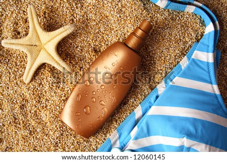 suntan lotion container on sand - stock photo