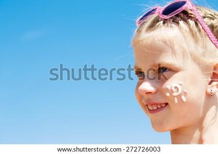 Suntan lotion girl applying sunscreen solar stream. Beautiful happy cute girl applying suntan cream on her face over ocean background. Sun tanning. Skin care and protection. Vacation - stock photo
