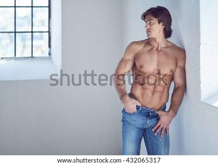 Suntanned muscular male in blue jeans posing in natural light from window. - stock photo