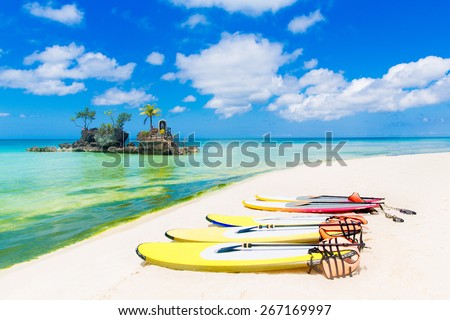 SUP surfing boards lie on a sandy tropical beach. Sea and island in the background. Summer vacation concept . - stock photo