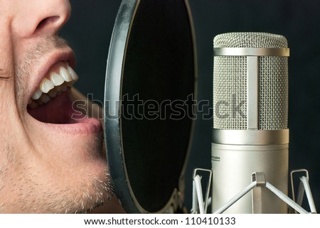 Super close-up of a man singing into a condenser microphone - stock photo