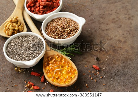 Super food - goji berries, chia seeds, flax seeds, walnuts and omega-3 capsules - stock photo