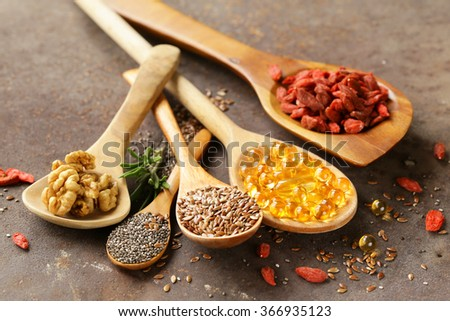 Super food - goji berries, chia seeds, flax seeds, walnuts and omega-3 capsules - stock photo