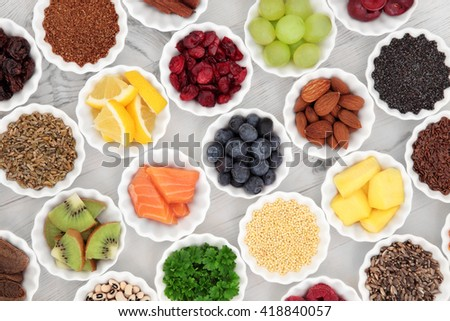 Super food selection in porcelain crinkle bowls over distressed wooden background. High in vitamins, anthocyanins and antioxidants. - stock photo