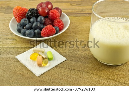 Super foods, anti-oxidant supplements and a cup of soy milk on wooden table - stock photo