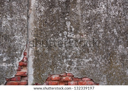 Super-grungy old exterior wall stained with fungus and moss. Broken plaster reveals a few layers of red bricks. - stock photo