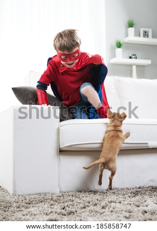 Super hero boy and chihuahua dog playing in the living room. - stock photo