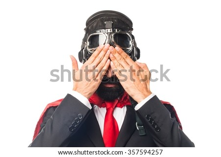 Super hero businessman covering his eyes - stock photo