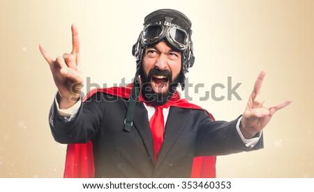 Super hero businessman making horn gesture - stock photo