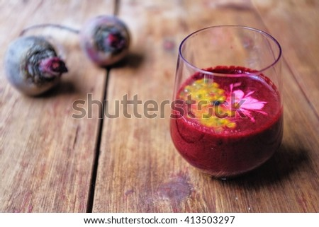 Super revival red breakfast drink; Mixed raspberry, strawberry and beetroot smoothie top with passion fruit . Soft focus on smoothie glass on wooden table. - stock photo
