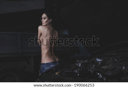 Super sexy chick behind the engine in open hood of old american car - stock photo