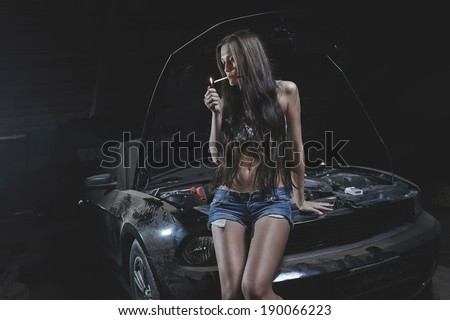 Super sexy chick smoking on the hood of old muscle american black car in garage - stock photo
