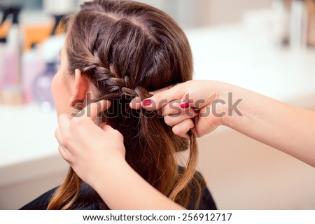 Super styling. Rear view closeup of a hairdresser braiding her clients hair in trendy weave plait while sitting in hairdressing salon - stock photo
