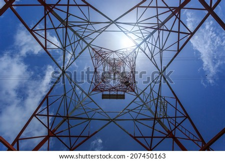 Super wide angle photograph of Electricity pylon with blue sky and sun - stock photo