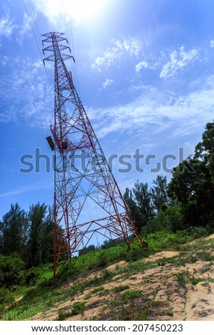 Super wide angle photograph of Electricity pylon with blue sky and sun, , tilted horizon - stock photo