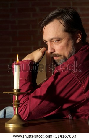 Superb man sits quietly at his home at the table - stock photo
