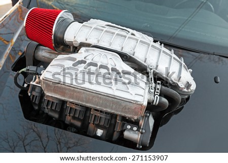Supercharger, air compressor that increases the pressure or density of air supplied to an internal combustion car engine to get additional extra power, closeup photo with selective focus, shallow DOF - stock photo