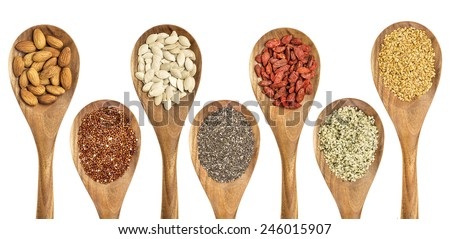 superfood abstract - isolated wooden spoons with almonds, red quinoa grain, pumpkin seeds, chia seeds, goji berry, hemp seed hearts, and golden flax seed - stock photo