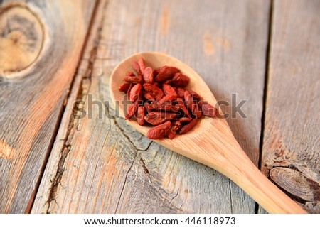 Superfood goji berries on a spoon on wooden table - stock photo