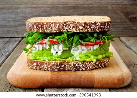 Superfood sandwich with avocado, egg whites, radish and pea shoots on whole grain bread against a rustic wood background - stock photo