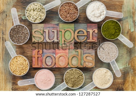 superfoods word in letterpress wood type surrounded by plastic scoops of healthy seeds and powders (chia, flax, hemp, pomegranate fruit powder, wheatgrass, whey protein, maca root) - top view - stock photo